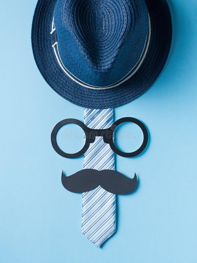 Begrepp f?r faderdag med hatten, exponeringsglas och bandet p? bl? bakgrund royaltyfria foton