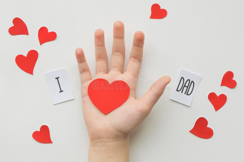 Begrepp f?r faderdag Meddelande med pappers- hjärta i barns hand på vit bakgrund Top besk?dar F?delsedag royaltyfri fotografi