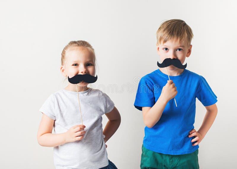 Begrepp f?r faderdag, tv? lilla caucasian ungar med mustaschen p? vit bakgrund fotografering för bildbyråer