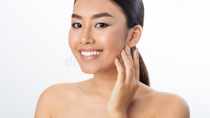 Begrepp f?r hudomsorg Asiatisk kvinna som ler till kameran arkivfoton