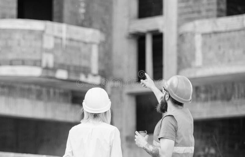 Begrepp f?r konstruktionslagkommunikation diskutera plan Den kvinnateknikern och byggm?staren meddelar p? konstruktionsplatsen arkivfoto