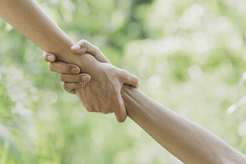 Begrepp f?r portionh?nder Hand som rymmer för hjälp på naturbakgrund arkivfoto