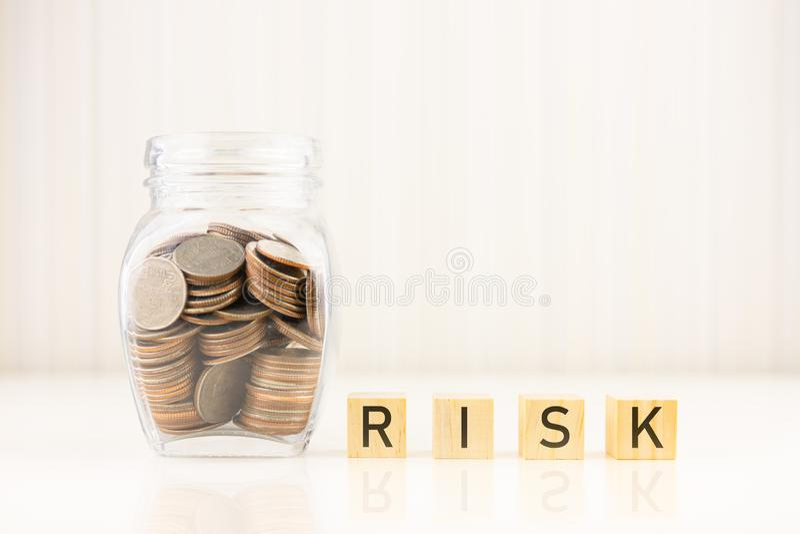 Begrepp f?r riskledning Mynt i krus med träsnittkubordet RISK royaltyfri bild