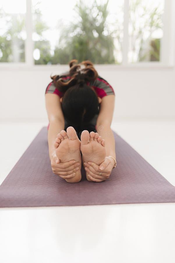 Begrepp f?r yoga f?r ung attraktiv yogikvinna som ?vande sitter i den Janu Sirsasana ?vningen, huvud f?r att kn?a den fram?t kr?k arkivfoto