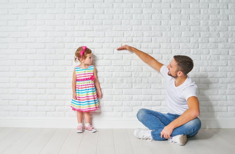 Begrepp Farsan mäter tillväxt av hennes barndotter på en vägg royaltyfri fotografi