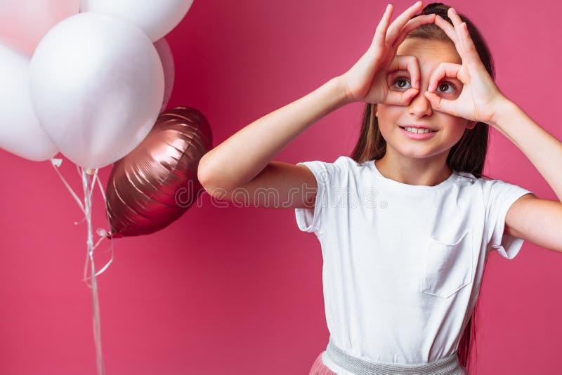 Begrepp: flickan visar exponeringsglas vid händer, stående av den tonårs- flickan på rosa bakgrund, med ballonger, födelsedagen royaltyfria bilder