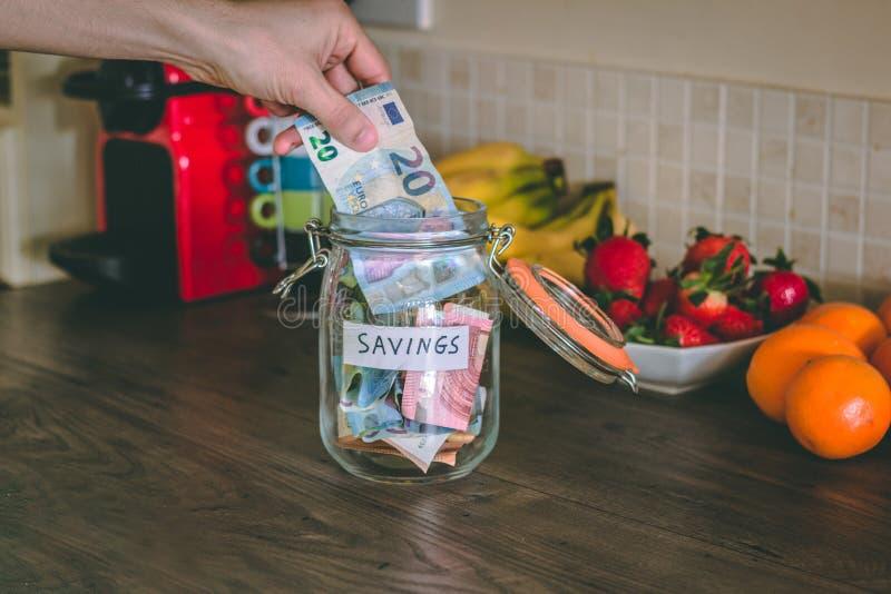 Begrepp: handen som förlägger pengar på besparingar, skorrar överst av tabellen för kök` s royaltyfria bilder