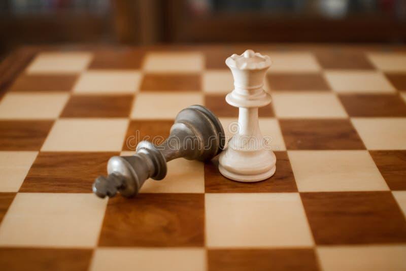 Begrepp: kvinnan som dominerar mannen Ett träschackbräde med konungen på jordningen efter schackmatten och drottningen royaltyfri bild