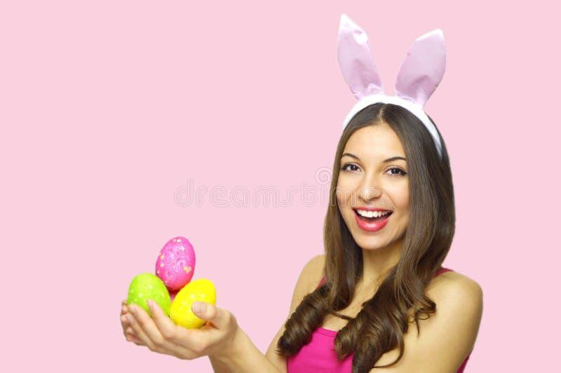 begrepp lyckliga easter Den lyckliga gladlynta kvinnan med kaninen gå i ax hållande färgrika påskägg som ser kameran över rosa ba royaltyfri fotografi