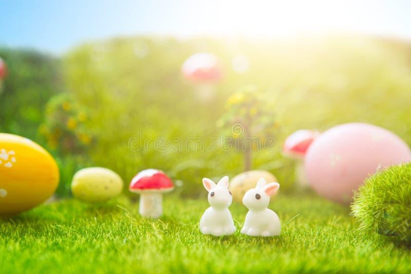 begrepp lyckliga easter Påskkaniner leker med easter ägg på grönt gräs Sagasolnedgång på det plast- gröna fältet med plast arkivfoto