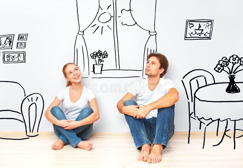 Begrepp: lyckliga par i ny lägenhet drömmer och planerar inre royaltyfri foto