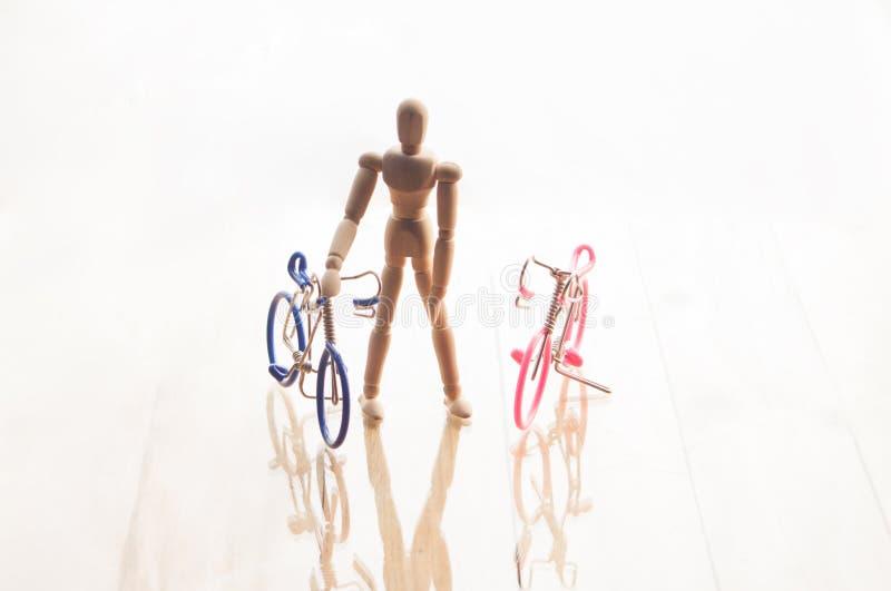 Begrepp med den trämänskliga attrappen och cyklar på vit b royaltyfri foto