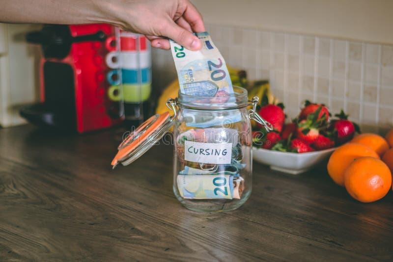 Begrepp: räcka att förlägga pengar på en förbanna krus överst av tabellen för kök` s royaltyfri foto