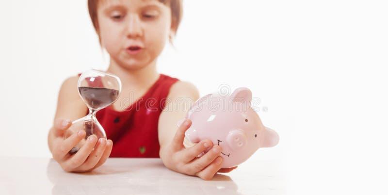 Begrepp: tid ?r pengar Humoristisk stående av den gulliga lilla affärsbarnflickan som rymmer en sandklocka och spargris royaltyfri fotografi