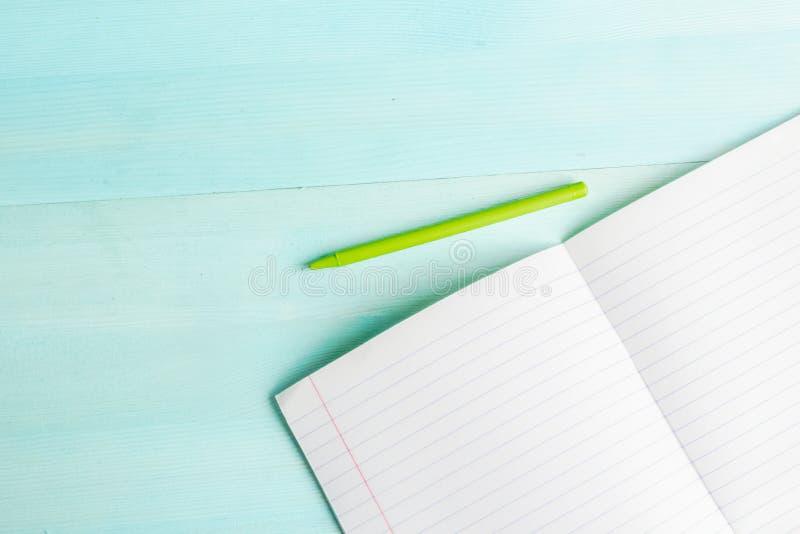 Begrepp tillbaka till skolan Skolatillbehör, kulöra blyertspennor, penna med den tomma anteckningsboken på blå träbakgrund arkivbild