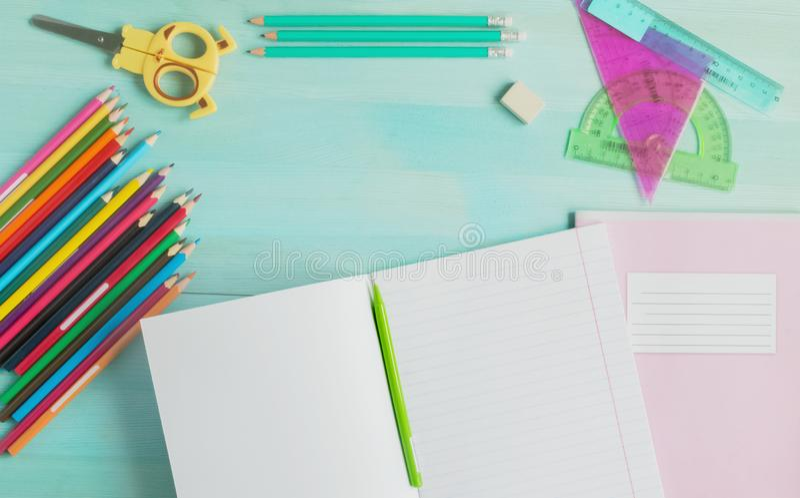 Begrepp tillbaka till skolan Skolatillbehör, kulöra blyertspennor, penna med den tomma anteckningsboken på blå träbakgrund royaltyfri foto