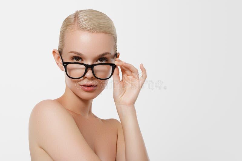 Begreppet av affären och att lära En trevlig le blond flicka med svarta exponeringsglas hipster Ungt mode och skönhet royaltyfria foton