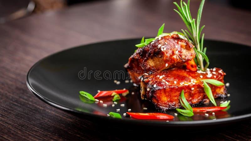 Begreppet av amerikansk kokkonst Stöd för grillat griskött, bakat och glasat i grillfestsås portiondisk i restaurangen royaltyfri bild