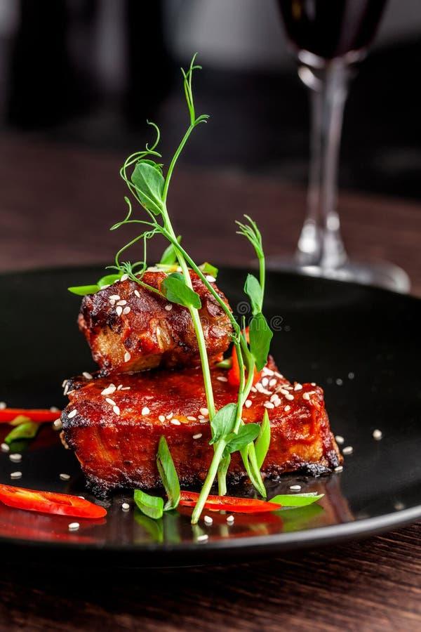 Begreppet av amerikansk kokkonst Stöd för grillat griskött, bakat och glasat i grillfestsås portiondisk i restaurangen royaltyfria foton