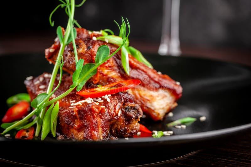 Begreppet av amerikansk kokkonst Stöd för grillat griskött, bakat och glasat i grillfestsås portiondisk i restaurangen royaltyfri fotografi