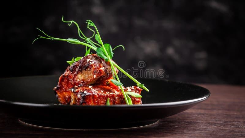 Begreppet av amerikansk kokkonst Stöd för grillat griskött, bakat och glasat i grillfestsås portiondisk i restaurangen arkivbild