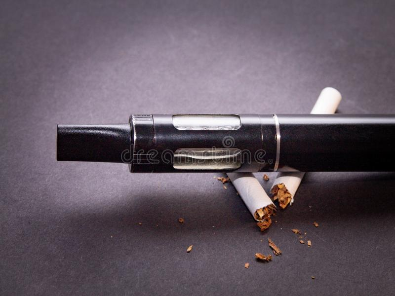 Begreppet av anti- - att röka sprejflaskan är på cigarettisolaten på mörk bakgrund royaltyfria bilder