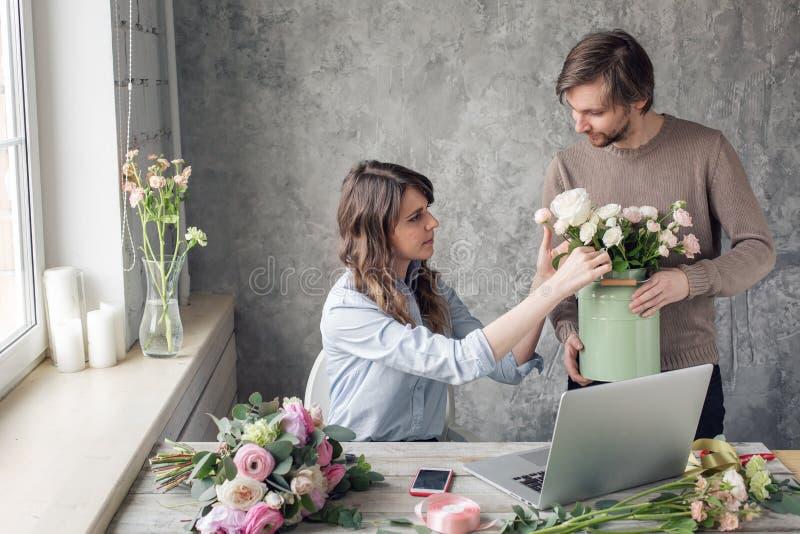 Begreppet av att arbeta i en blomsterhandel Beställning-ta och leverans Kvinnaägare och manassistent i blom- design royaltyfri foto