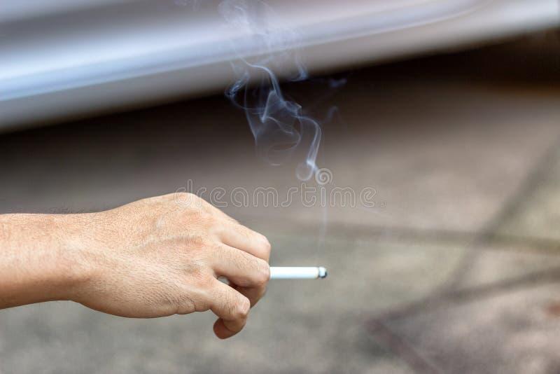 Begreppet av att röka upphörande med manliga händer bär rökcigarettdroger, som är skadliga till folk omkring och royaltyfri fotografi
