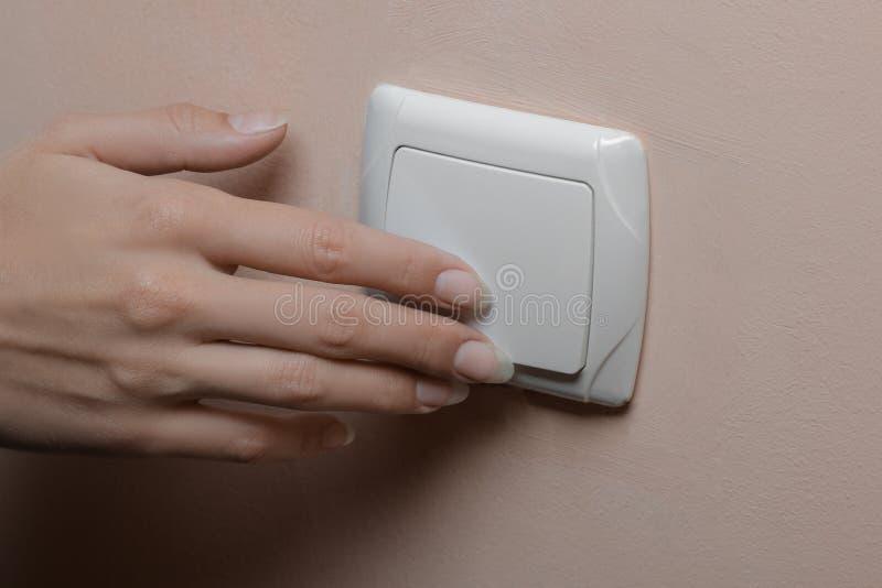 Begreppet av besparingelektricitet Flickan vänder av ljusen i rummet Närbild royaltyfria foton
