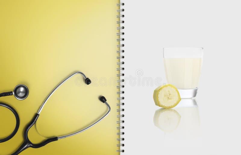 Begreppet av den allsidiga läkarundersökningen bantar med sund mat, pappersanteckningsboksidor med stetoskopet och fruktbananefru arkivbilder