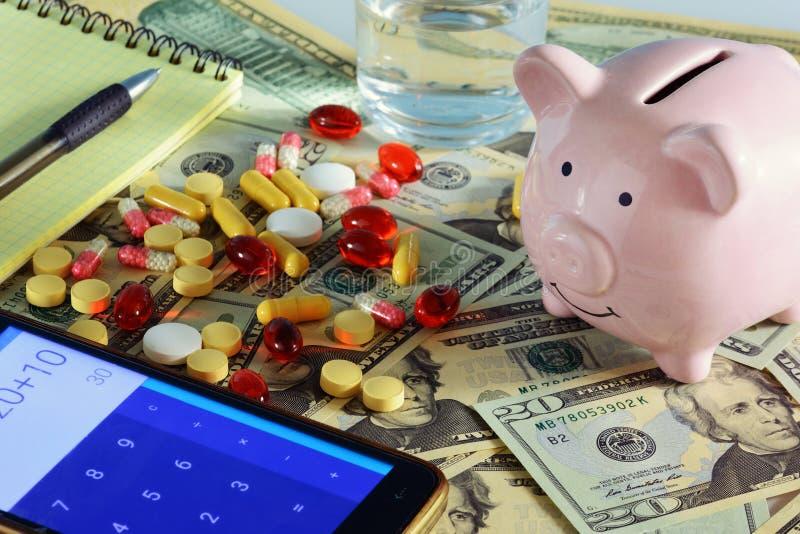 Begreppet av den dyra medetsinaen Foto av en spargris, pengar och en medicin Telefonen har en räknemaskin fotografering för bildbyråer
