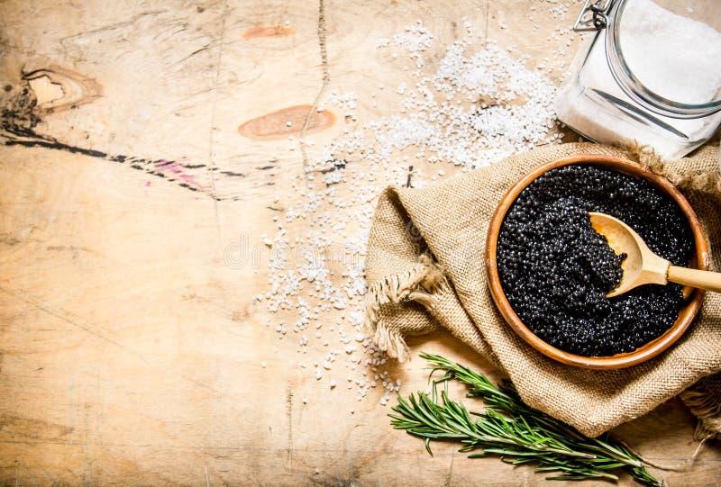 Begreppet av den svarta kaviaren Svart kaviar i kopp med salt och rosmarin arkivbild