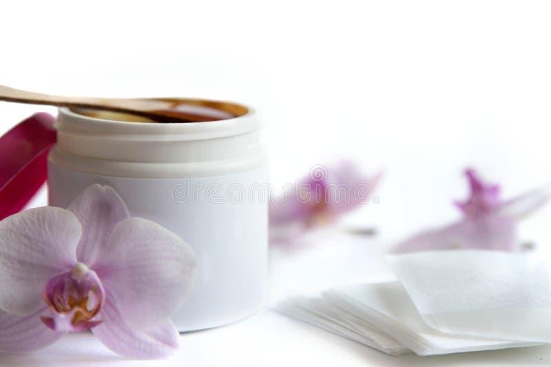 Begreppet av depilation och skönhet är vaxet för sockerdeg- eller hårborttagning i en vit plast- krus med en trävaxspatel, i smäl royaltyfri fotografi