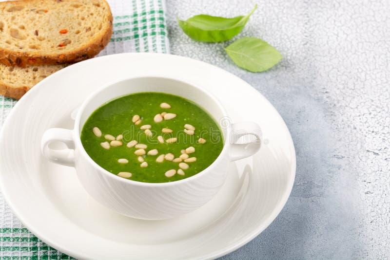 Begreppet av en sund, vegetarisk eller diet-mat: kräm- spenatsoppa, med sörjer muttrar och basilika Med skivor av vegetarian royaltyfria foton