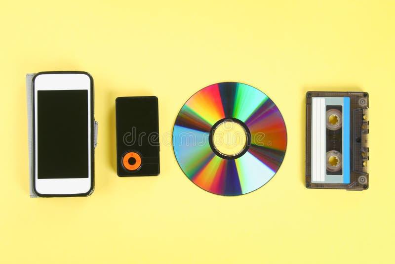 Begreppet av evolutionen av musik Kassett CD-skiva, mp3 spelare, mobiltelefon Tappning och modernitet Musikservice royaltyfri foto