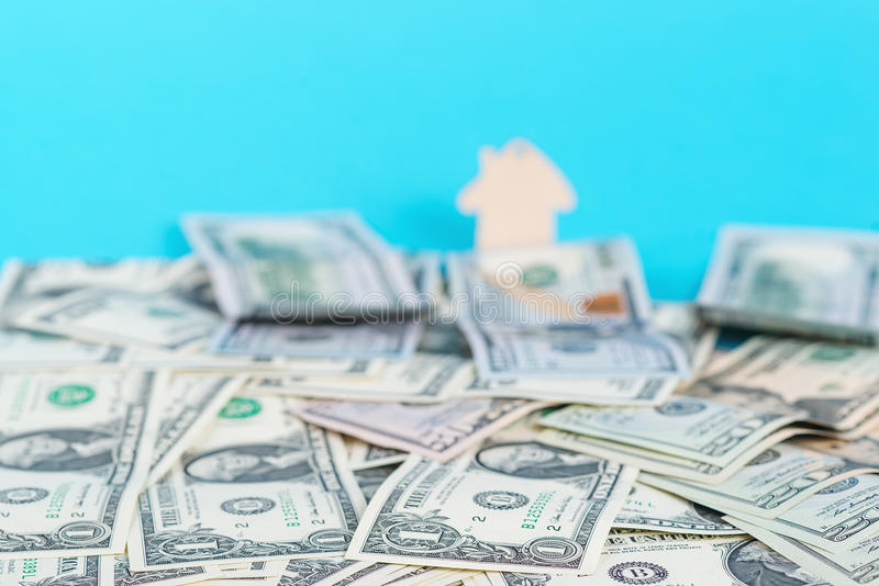 Begreppet av finansiella besparingar som köper ett hus Mini- modellhus bak pengarbakgrund royaltyfri foto