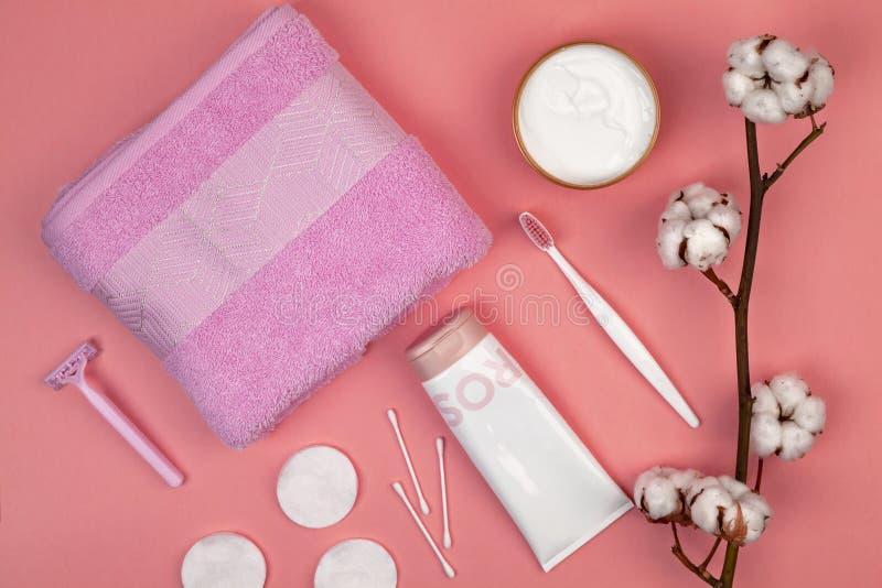 Begreppet av hudomsorg Bomullsblock för borttagningsmakeup, bomullsfilial, bomullsblock, örapinnar, rosa handduk Lekmanna- lägenh arkivbild