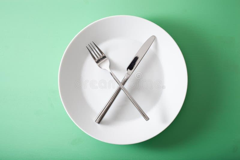 Begreppet av intermittent fasta och ketogenic bantar, viktförlust gaffeln och kniven korsade på en platta arkivfoton