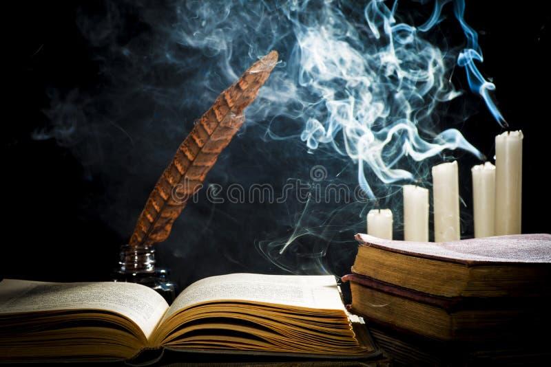 Begreppet av kunskap, en öppen bok och en bläckhorn med en penna arkivfoto