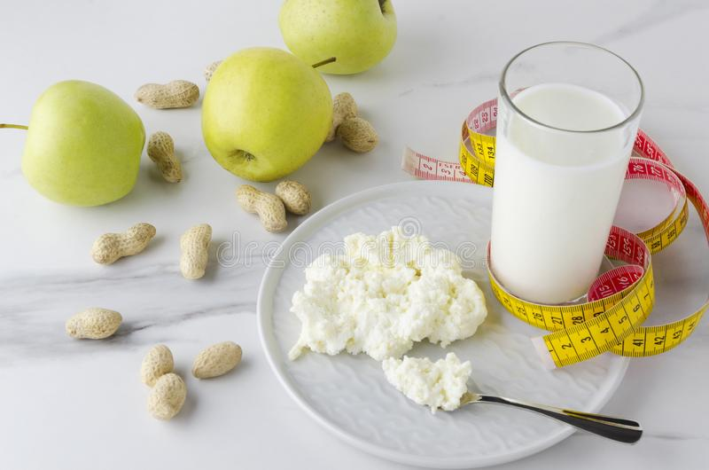 Begreppet av läckert mål för mjölkar bantar och förlustvikt Exponeringsglas av mjölkar, pläterar med keso, gröna äpplen, jordnött royaltyfria foton