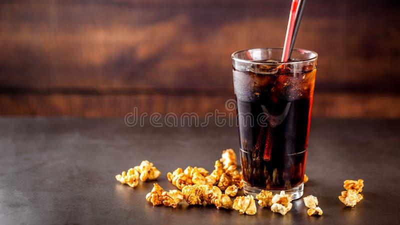 Begreppet av mat f?r bion, f?r att h?lla ?gonen p? en film Kall coladrink med is i ett exponeringsglas som fylls med popcorn arkivbild
