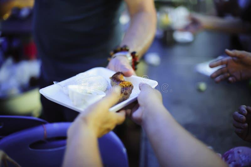 Begreppet av matning: H?nderna av det fattigt mottar mat fr?n h?nderna av det humant: Hj?lpa att mata det fattigt royaltyfria foton