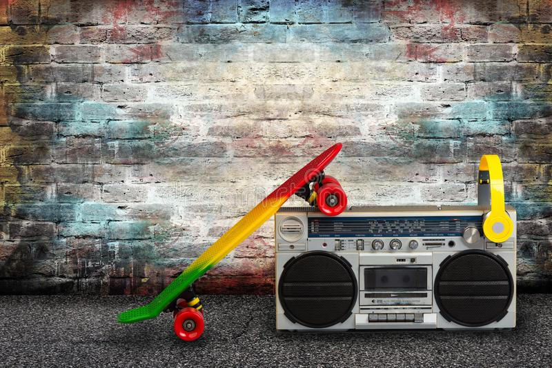 Begreppet av musiken Höftflygturstil Ljudsignal spelare för tappning med hörlurar och skateboarden på bakgrund för tegelstenvägg arkivbild