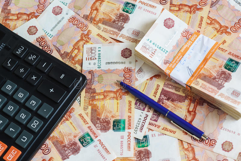 Begreppet av planläggningsinkomst och kostnader: räknemaskin och kulspetspenna och en packe av en halv miljon ryska rubel i banke arkivfoton