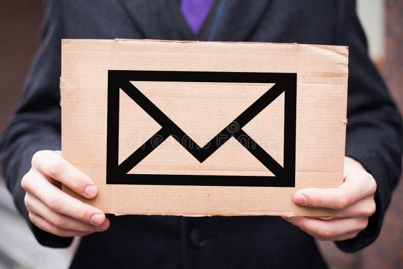 Begreppet av postgångar och bokstäver, post En man i en dräkt rymmer en platta med ett kuvertsymbol i hans händer royaltyfri bild