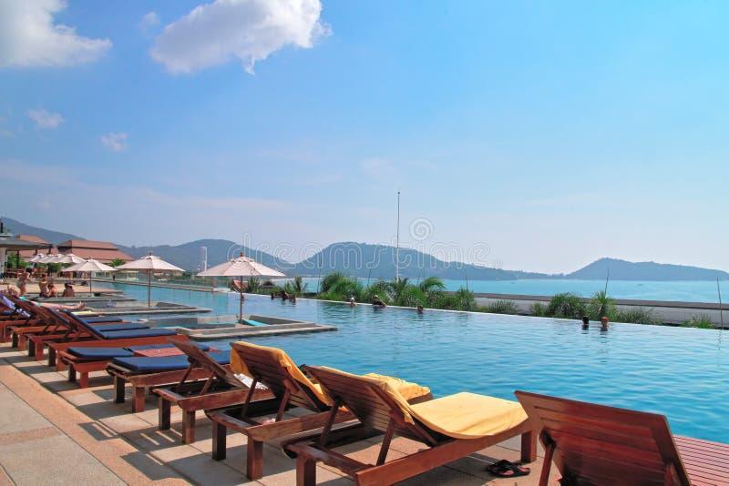 Begreppet av semestern för vilar den härliga lyxiga utomhus- pölen i hotellsemesterort med paraplyer och soldagdrivare blå havssk fotografering för bildbyråer