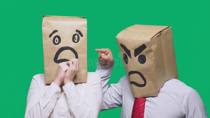 Begreppet av sinnesrörelser och gester Två personer i pappers- påsar med leenden Den aggressiva smileyen svär  arkivbilder