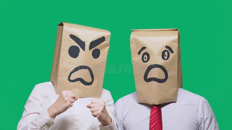 Begreppet av sinnesrörelser och gester Två personer i pappers- påsar med leenden Den aggressiva smileyen svär  arkivfoton