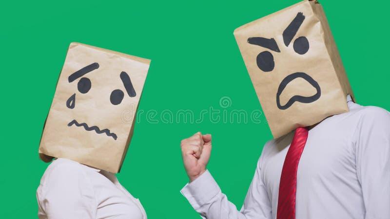 Begreppet av sinnesrörelser och gester Två personer i pappers- påsar med smileys Den aggressiva smileyen svär Den andra gråt arkivbild