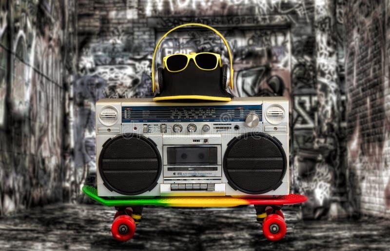 Begreppet av stilen för musikhöftflygtur Ljudsignal spelare för tappning med hörlurar Skateboard, trendigt lock och solglasögon royaltyfri foto